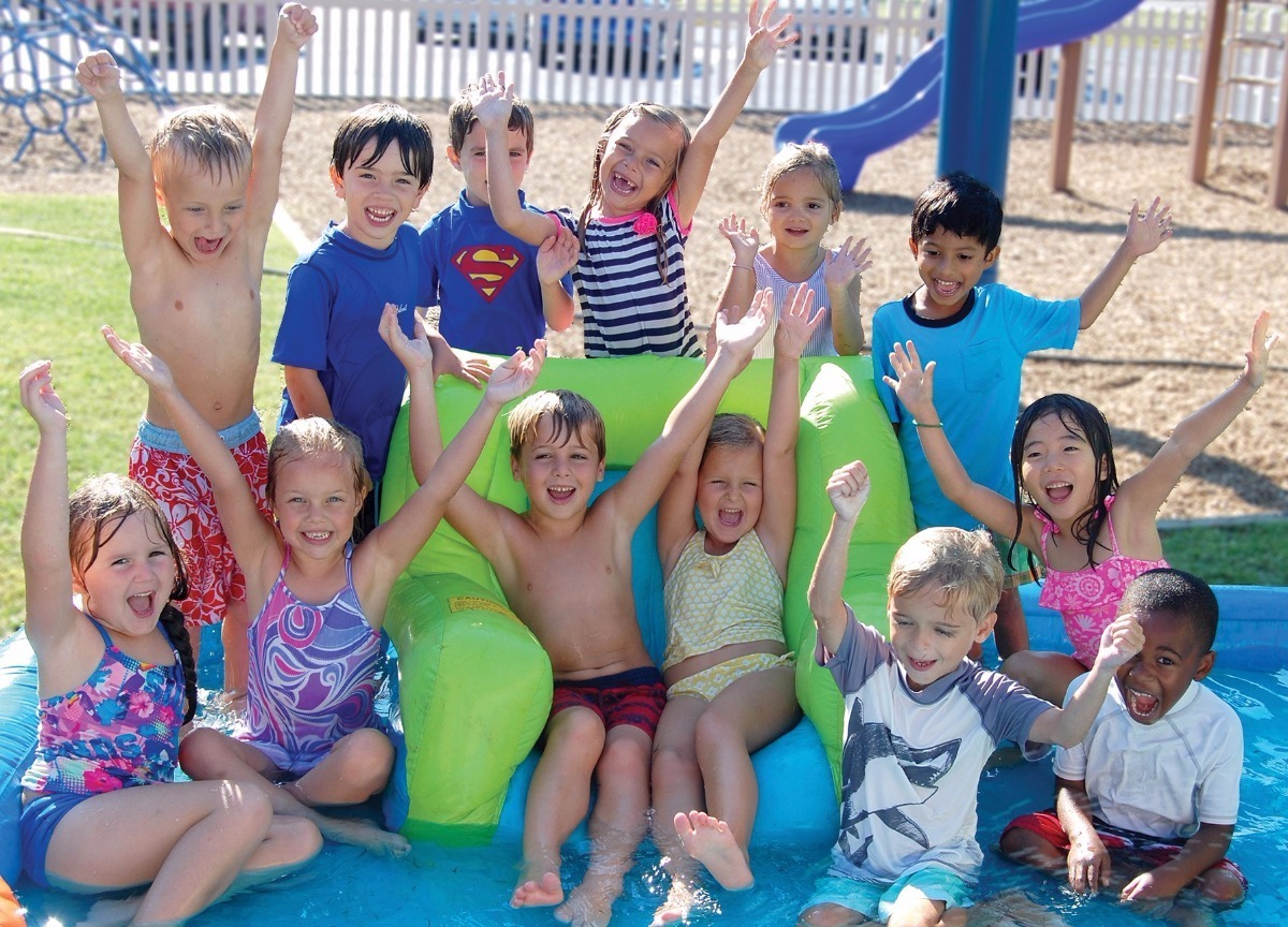 Summer Camp kids in water toy - arms up and happy