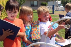 PreK kids exploring in the garden with clipboard and magnifying glass