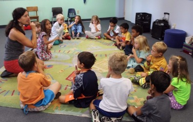 group of young children sitting in circle on floor in music class