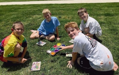 group of boys painting out on the grass