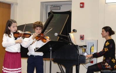 girl and boy playing violins and accompanied by teacher playing piano