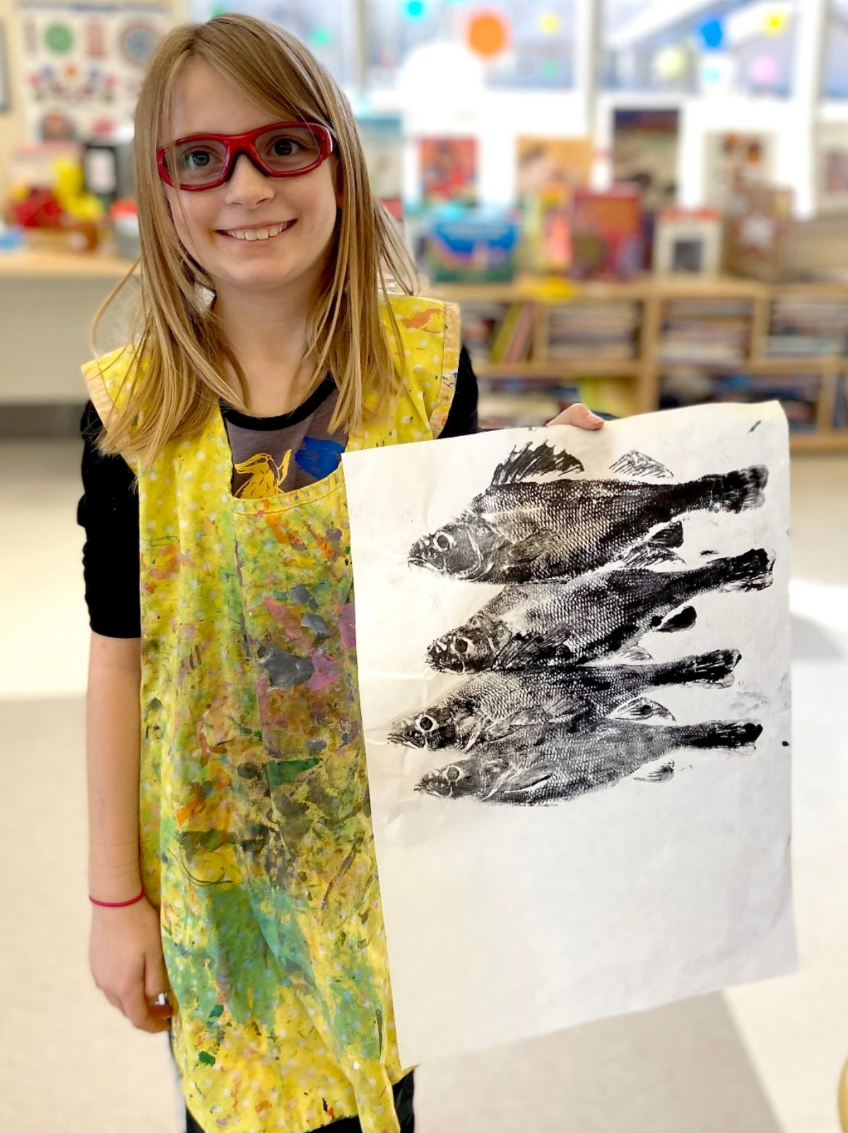 girl showing her painting of grass and flowers